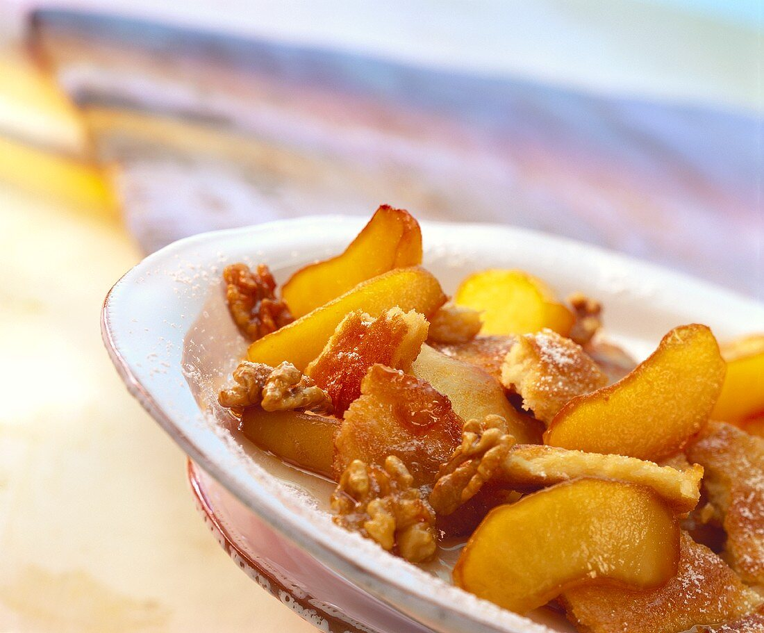 Apple pancake with walnuts and icing sugar