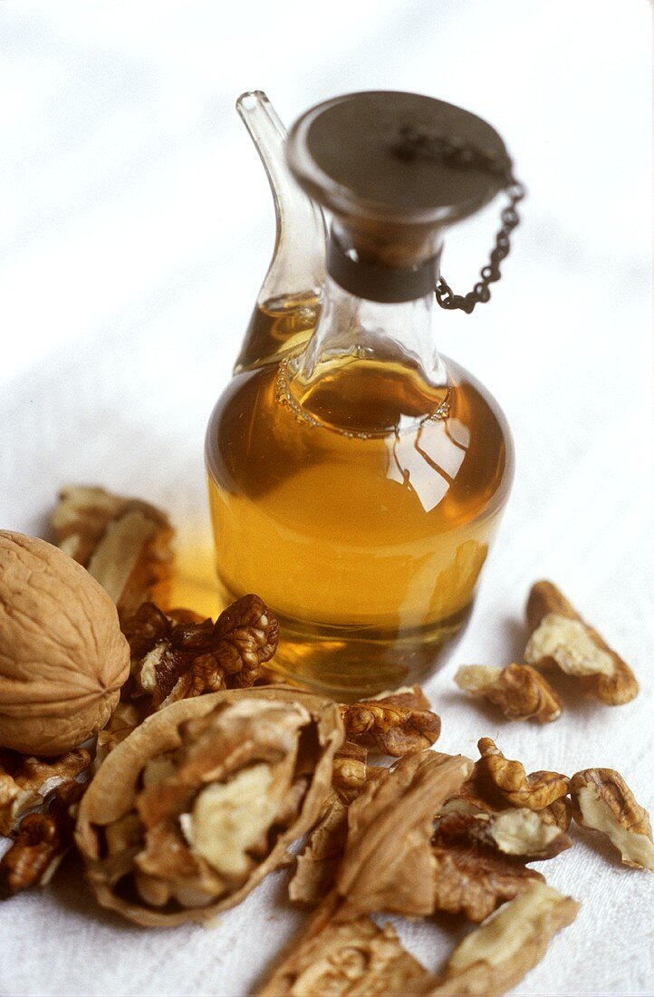 Walnut oil in glass jug surrounded by walnuts