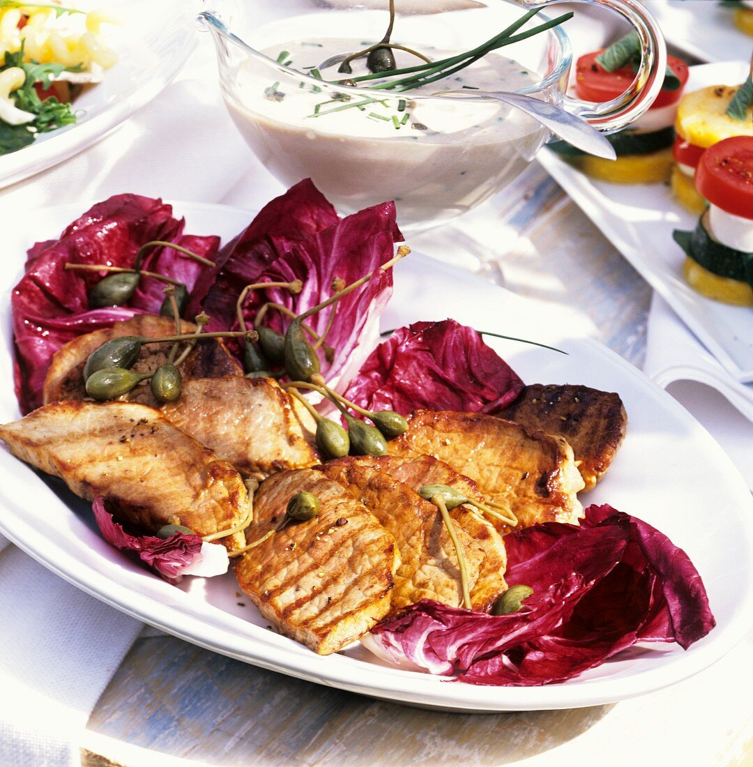 Grilled veal steaks with capers on radicchio; tuna cream