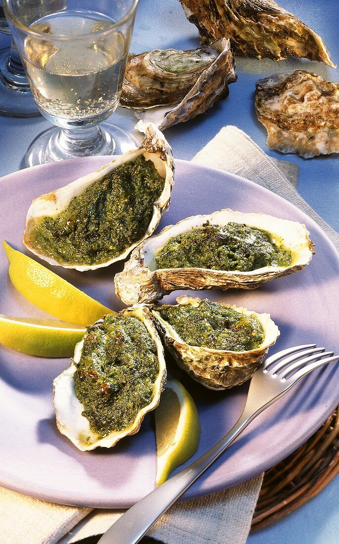 Baked oysters with lemon wedges; white wine