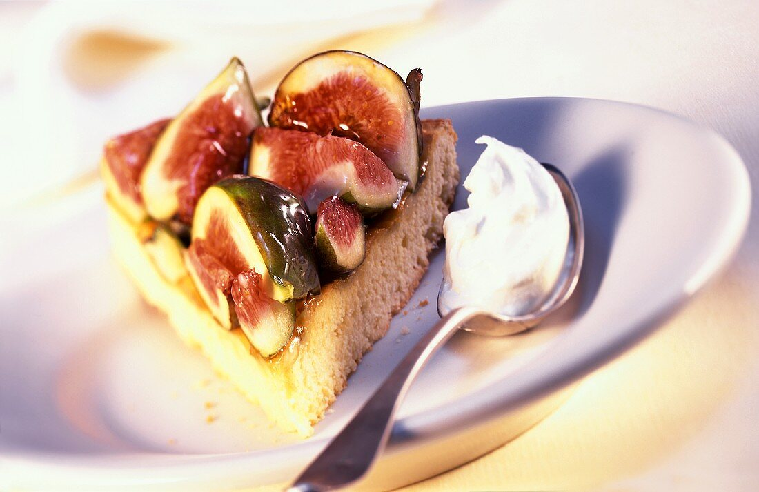 Piece of fig cake with a spoonful of cream
