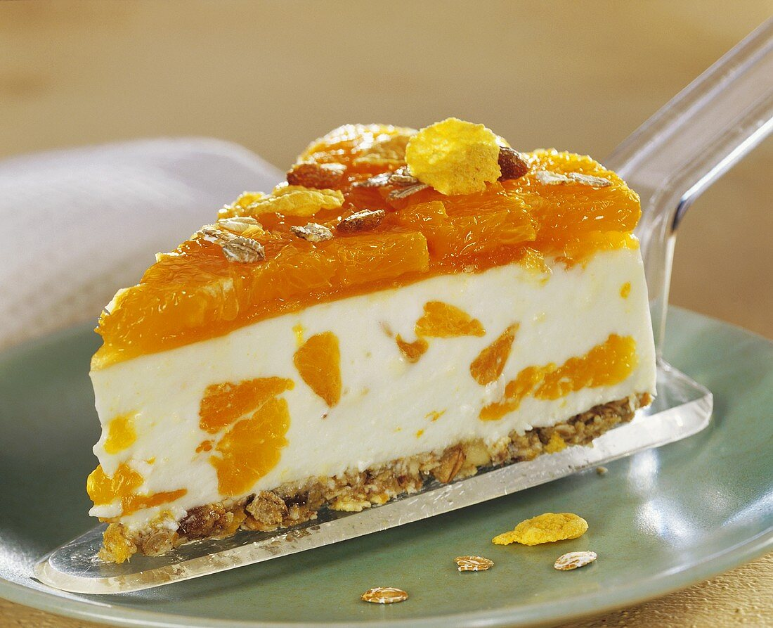 Piece of mandarin gateau with muesli on cake slice