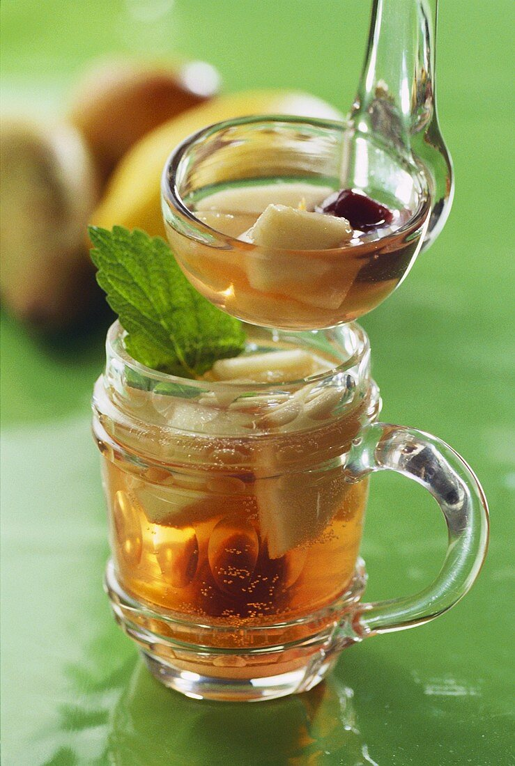 Cider punch in glass & ladle in front of apples & pears