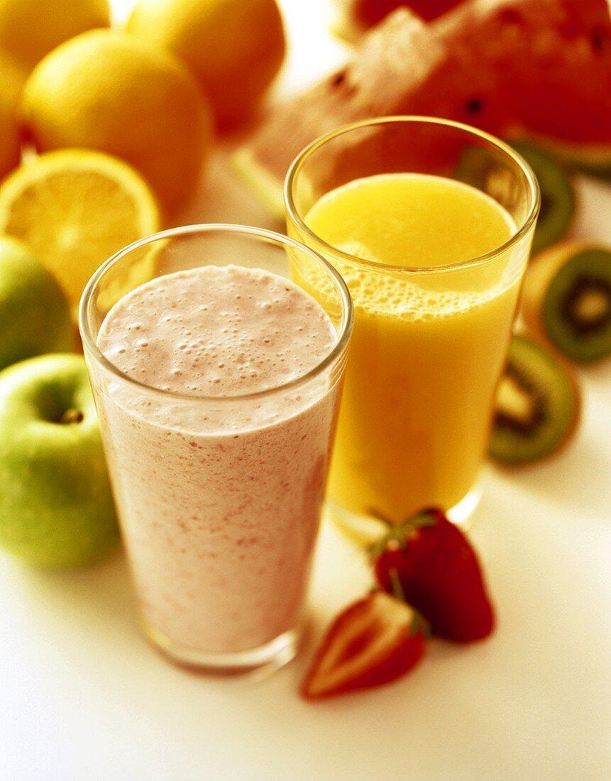 Strawberry milkshake and orange juice in front of fresh fruit