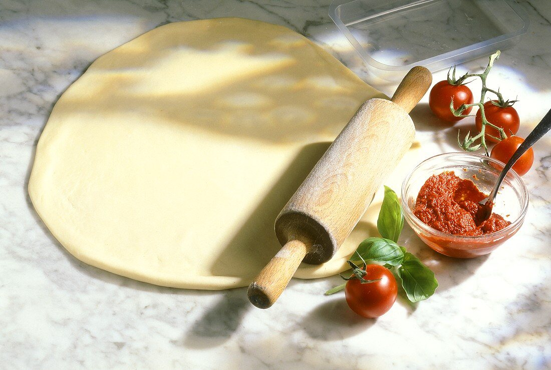 Rolled-out pizza dough, tomato sauce and fresh tomatoes
