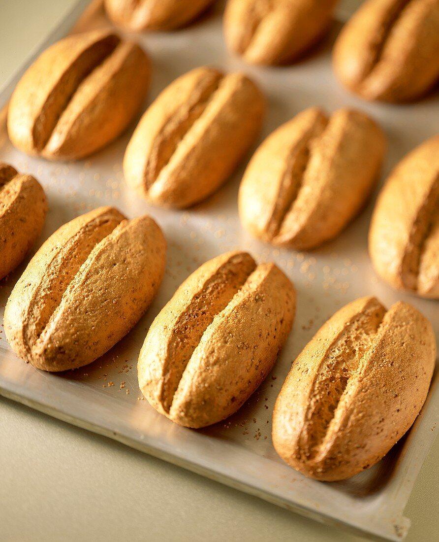 Several granary rolls on baking sheet