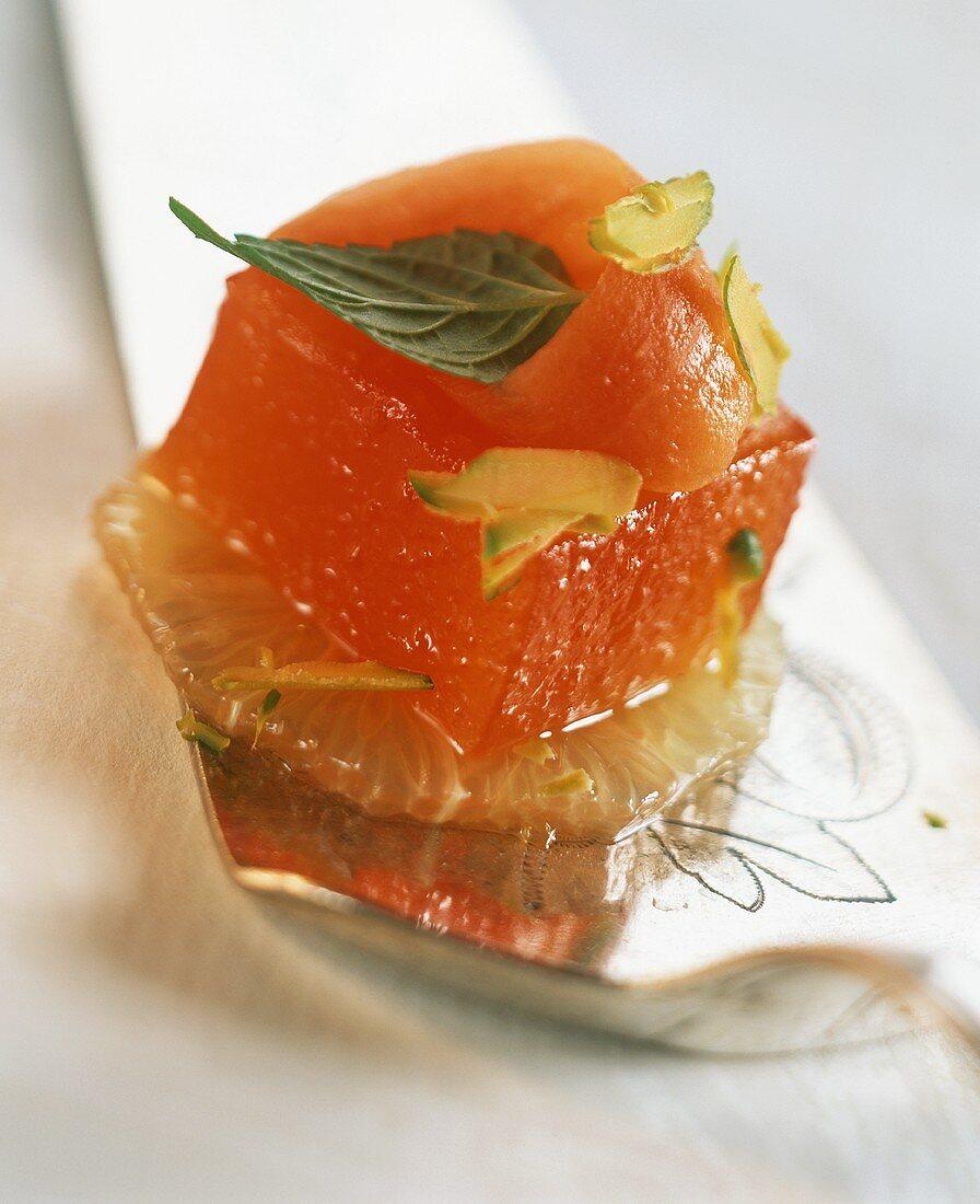 Blood orange jelly on grapefruit slice, decorated with papaya