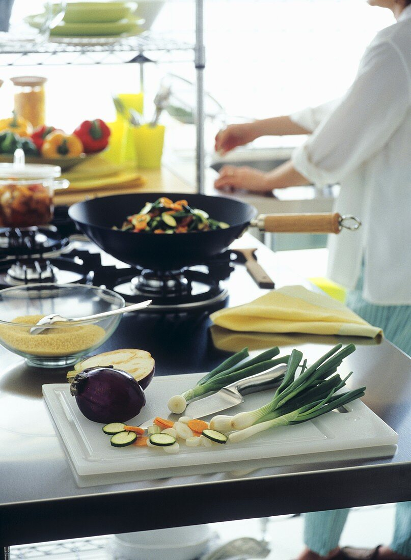 Kitchen scene with ingredients for wok dish and cook