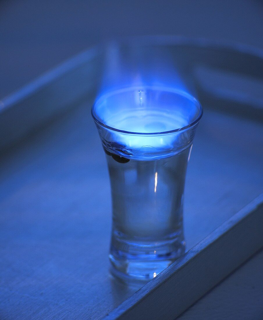 Flambéed Sambuca with coffee beans in glass