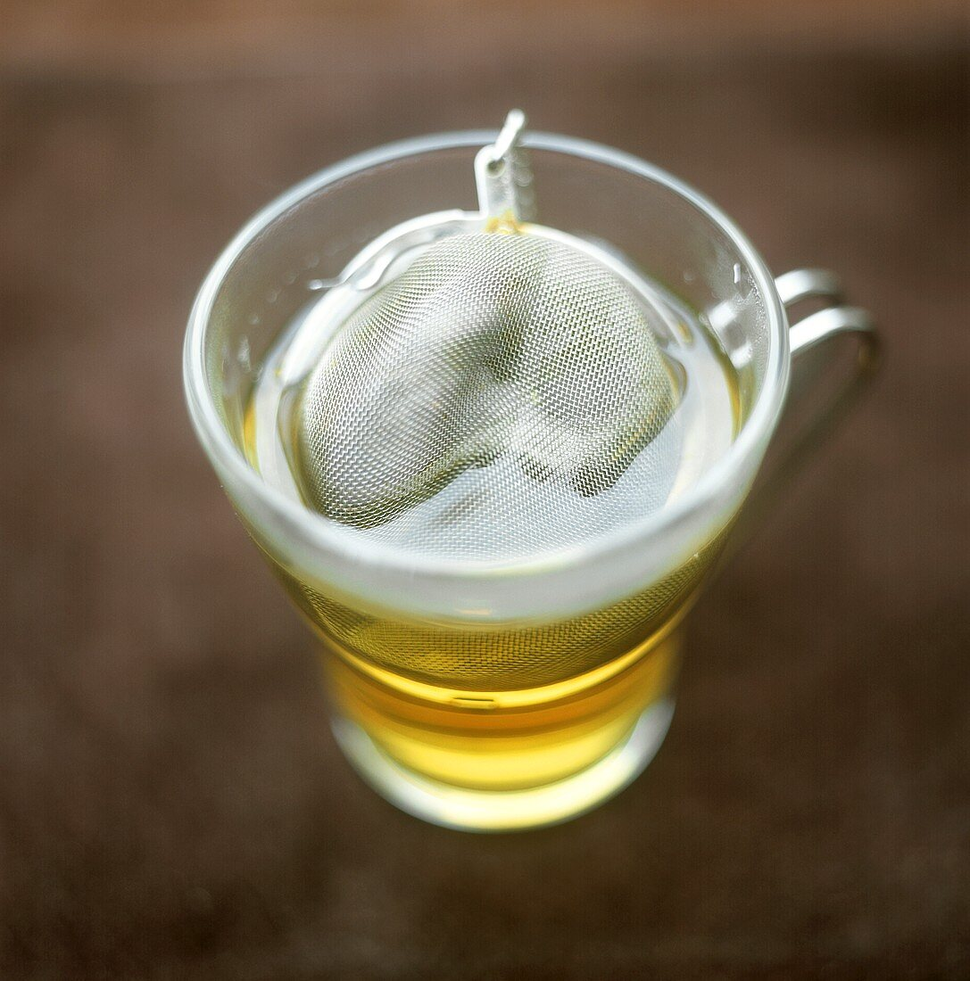 Green tea in glass cup with tea strainer