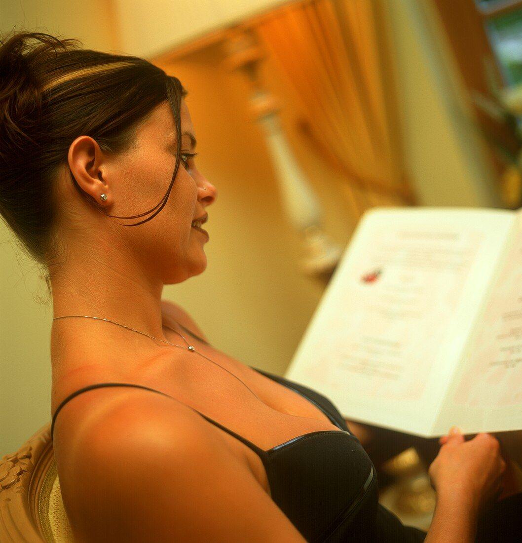 Woman in evening dress reading menu in restaurant