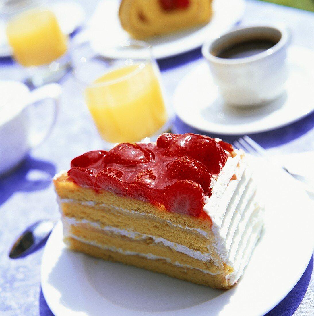 Piece of strawberry gateau, coffee & orange juice on table