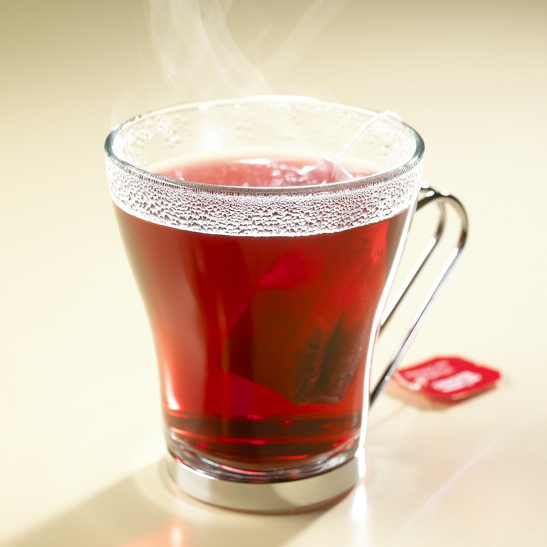 Steaming rose hip tea with tea bag in glass