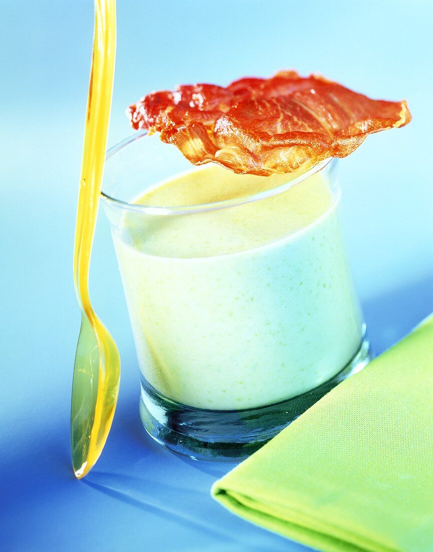 Pea soup in glass with fried rasher of bacon
