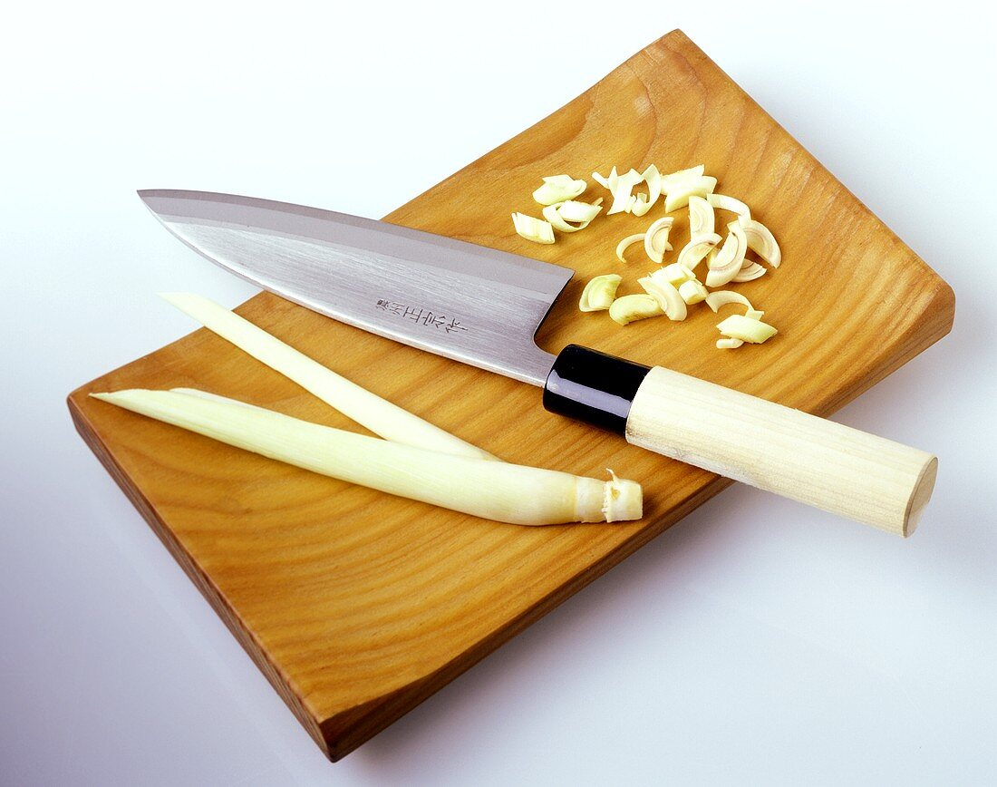 Lemon grass with Asian knife on wooden chopping board