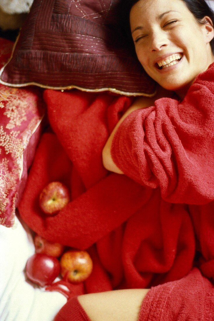 Young woman in red bathrobe with fresh apples