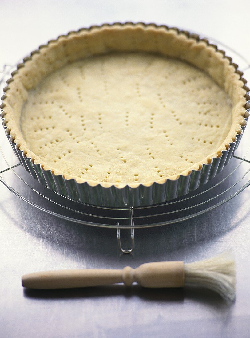Pricking shortcrust pastry base with fork