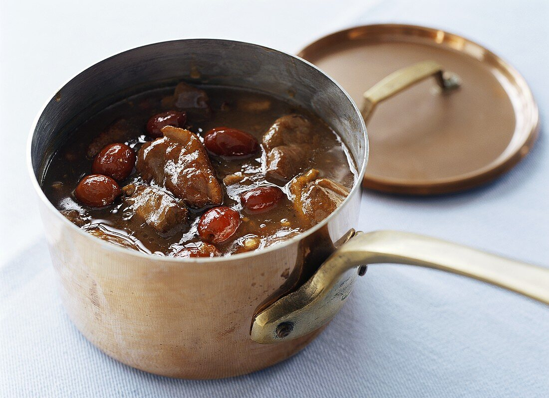 Duck curry with dates in copper pan