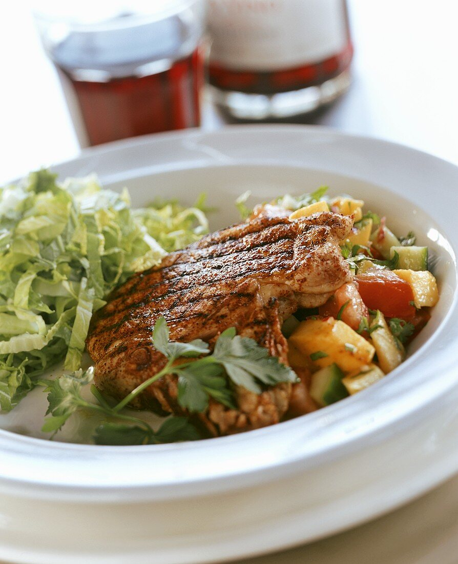 Grilled pork chop with mango salsa and salad