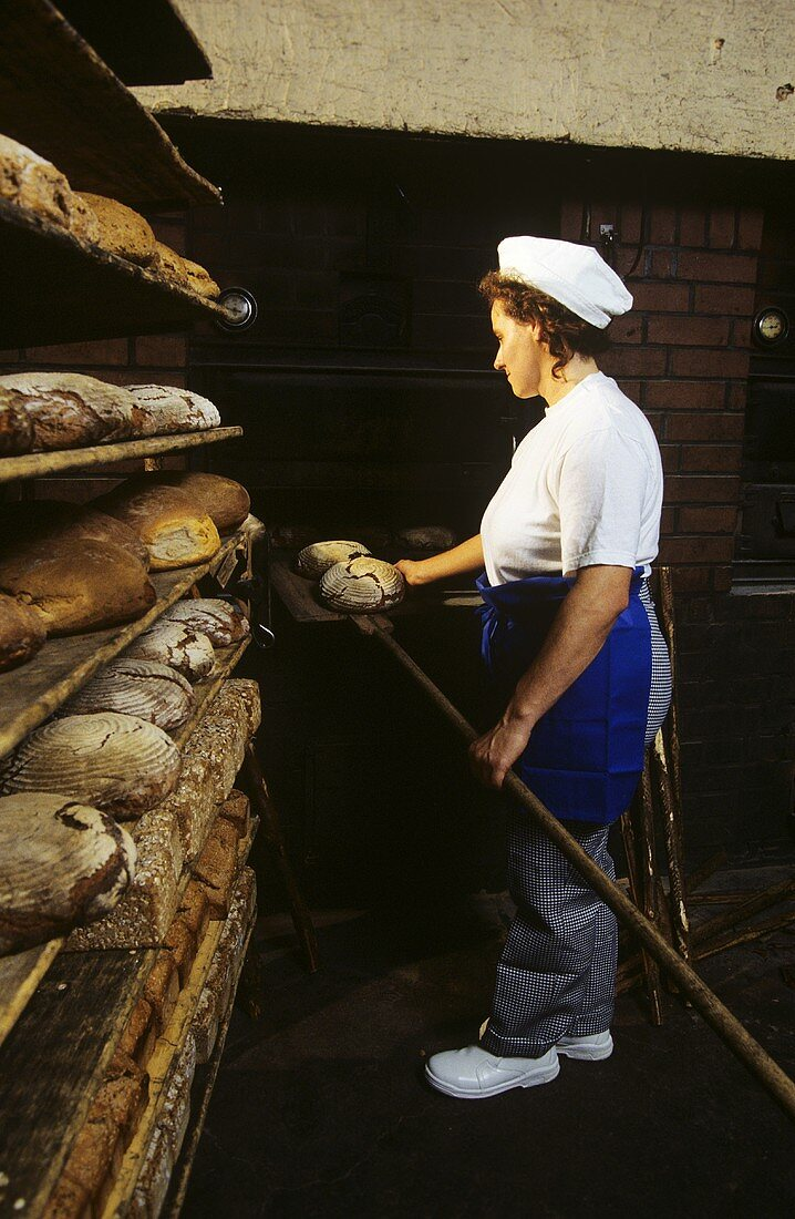 Female baker taking bread out of the oven in the bakery