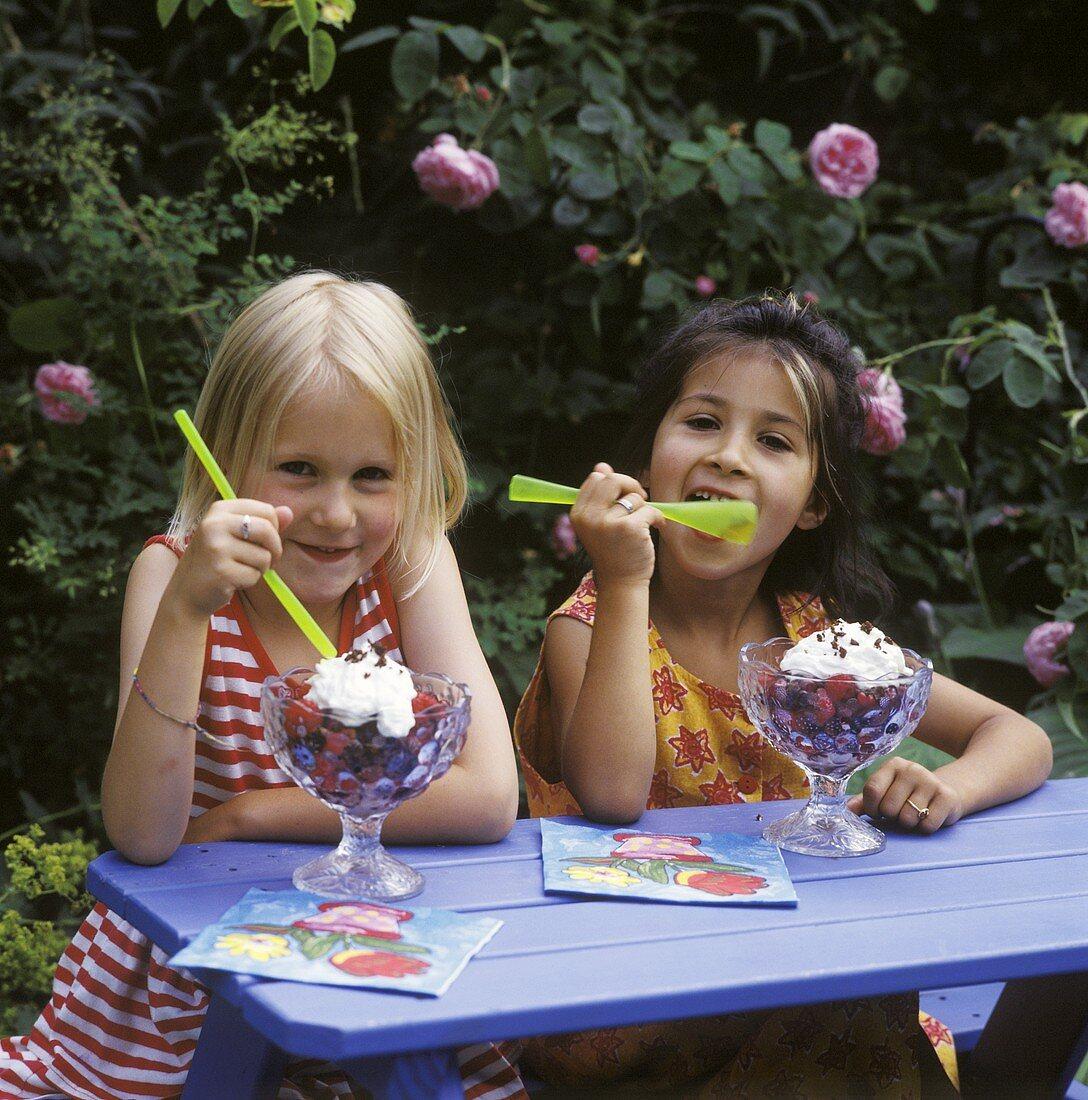 Two girls eating berry dessert out of sundae glasses