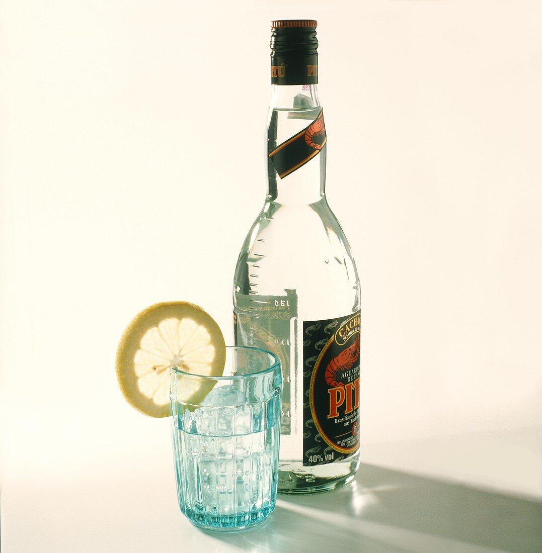 A bottle and a glass of Pitu (spirit base for Caipirinha)