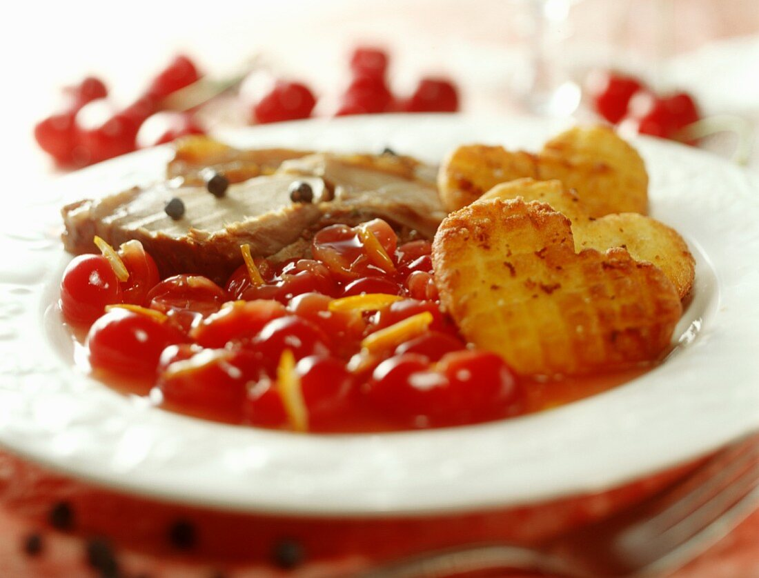 Wild boar cutlet with cherry sauce and potato cakes