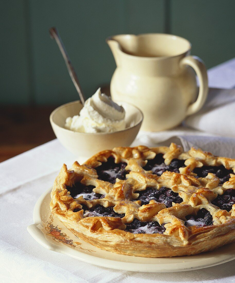 A blueberry tart with a bowl of whipped cream beside it