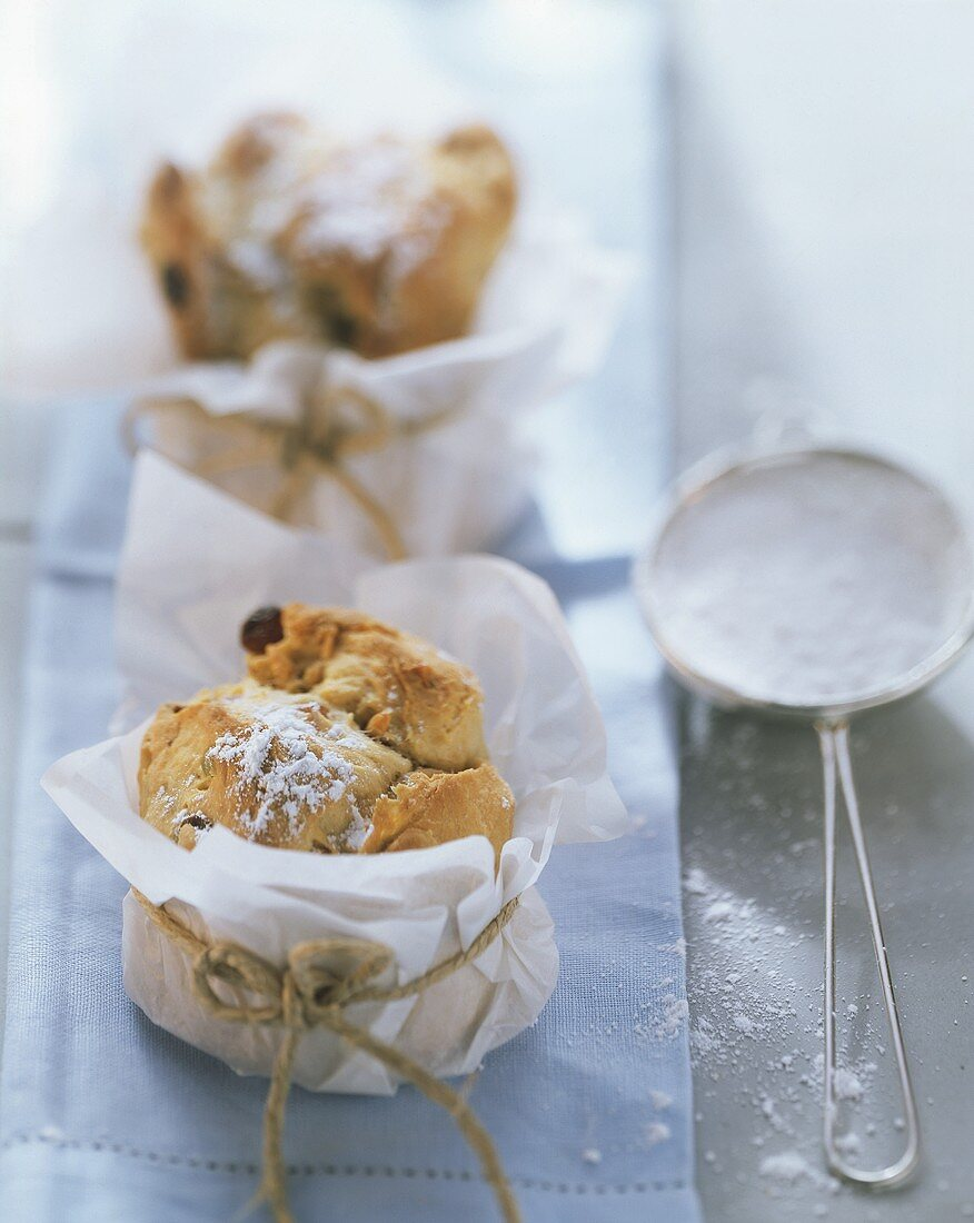 Small panettone with almonds & icing sugar in baking parchment