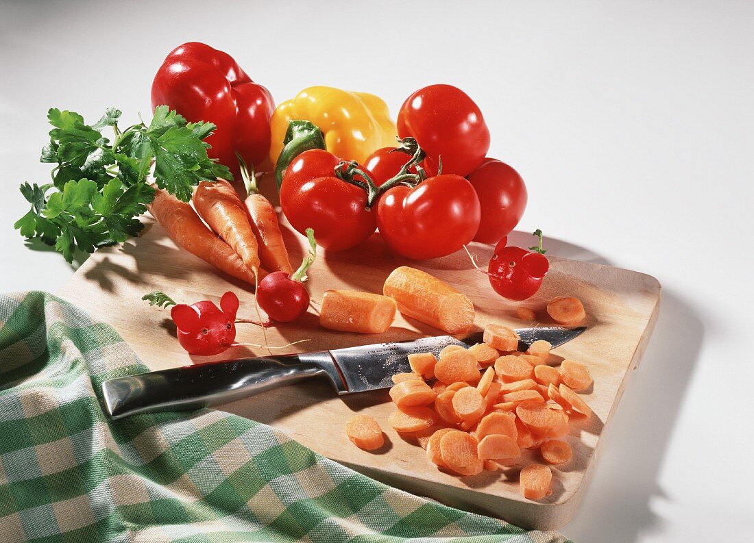 Carrots, tomatoes and peppers with knife on a board