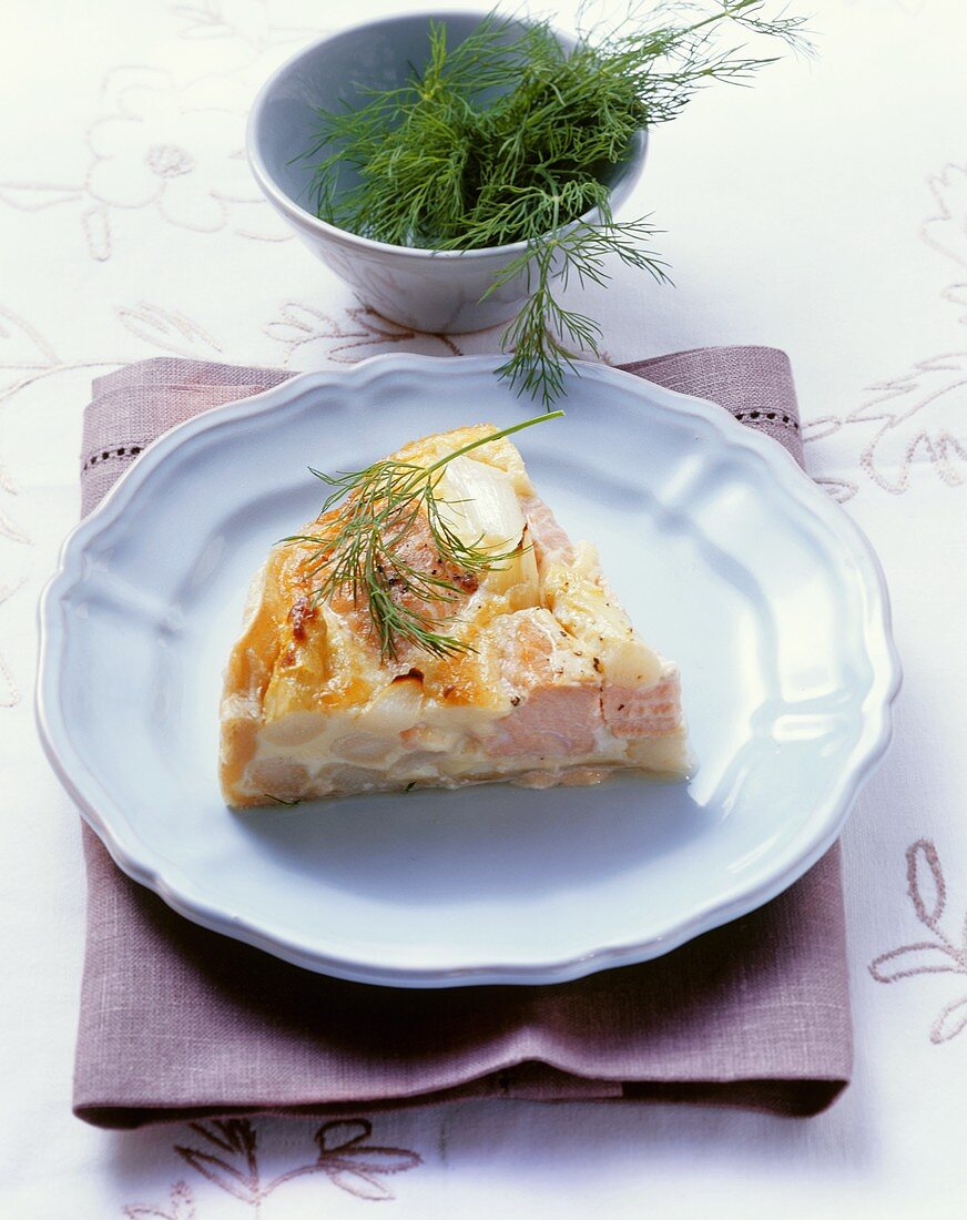 Piece of salmon and asparagus quiche with fresh dill