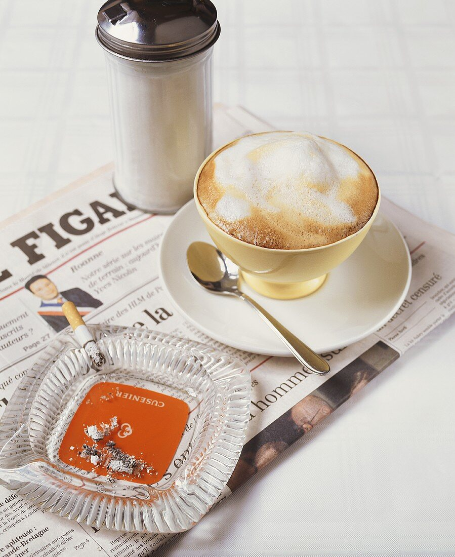 Cup of cappuccino, cigarette and French newspaper