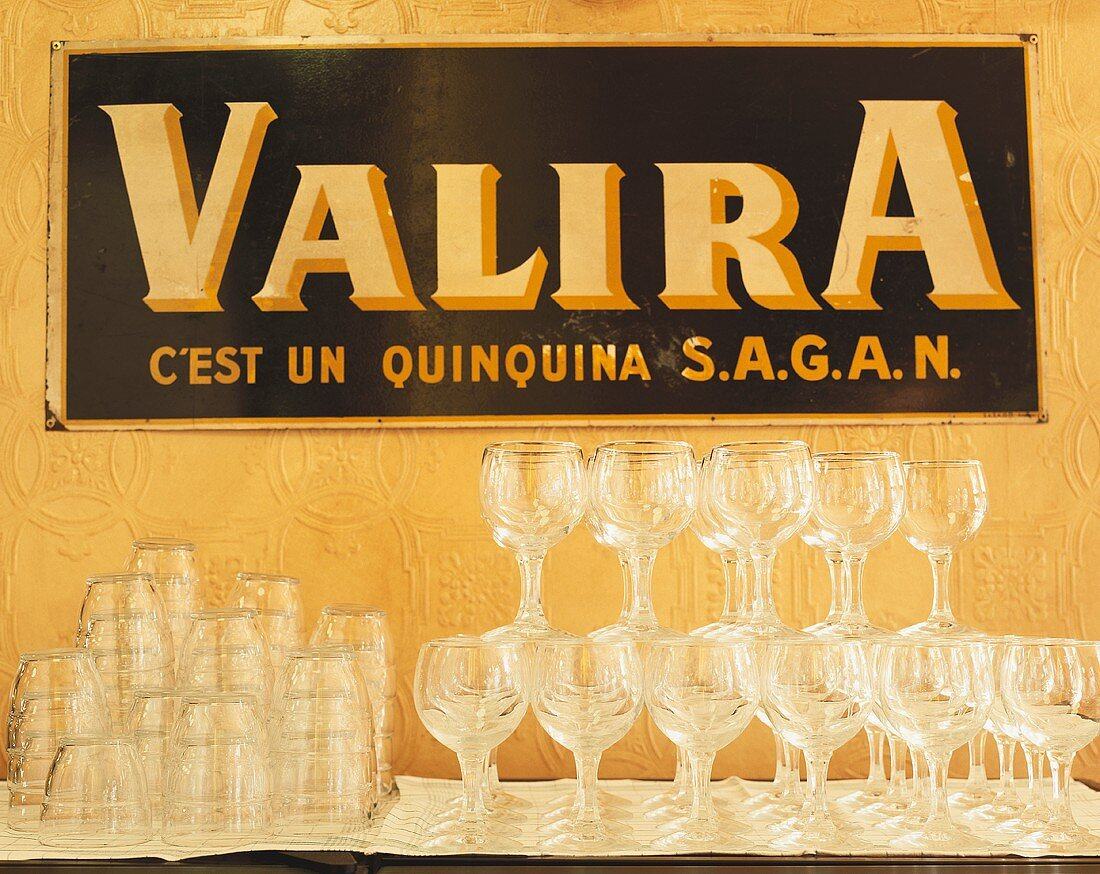 Empty wine & water glasses in front of Valira publicity sign