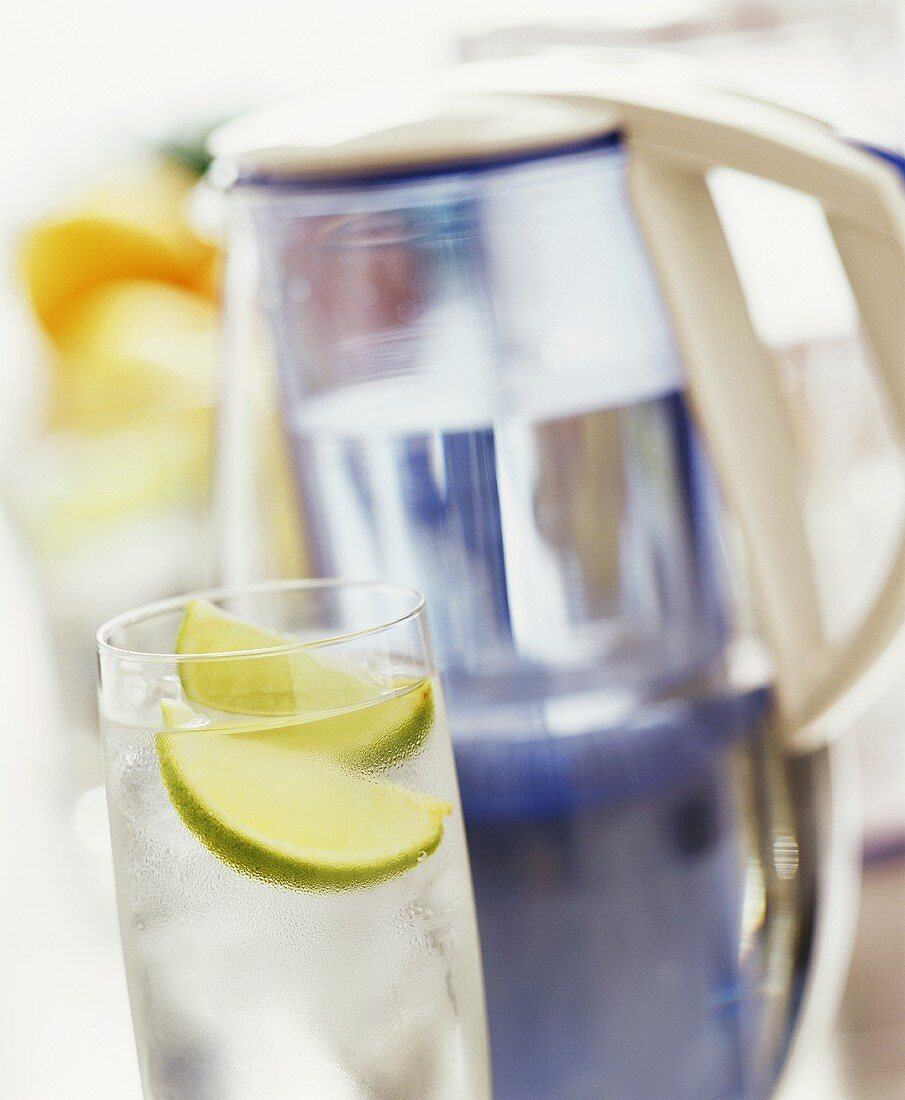 Glass of water with lime and jug with water filter