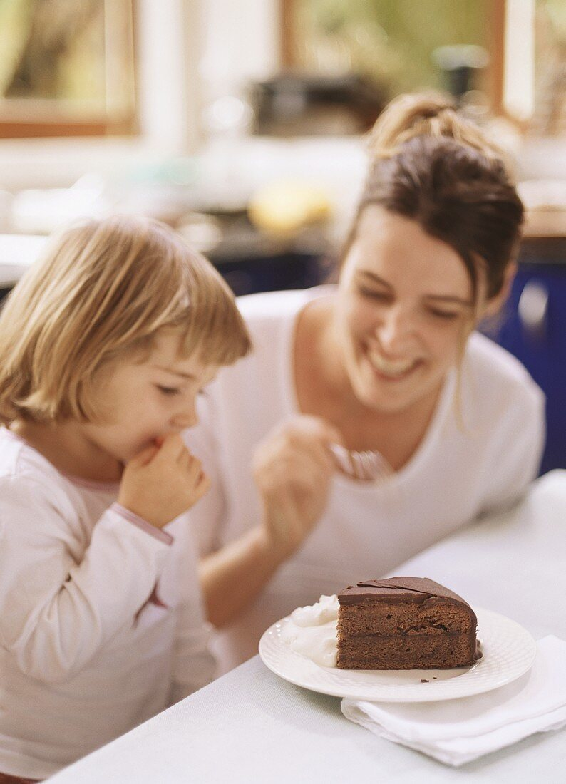 Mother and small daughter eating piece of Sacher torte