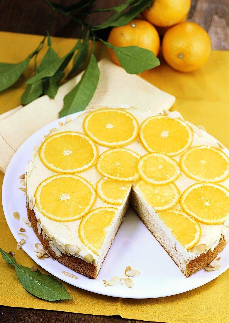 Orange cream cake with flaked almonds, a piece taken