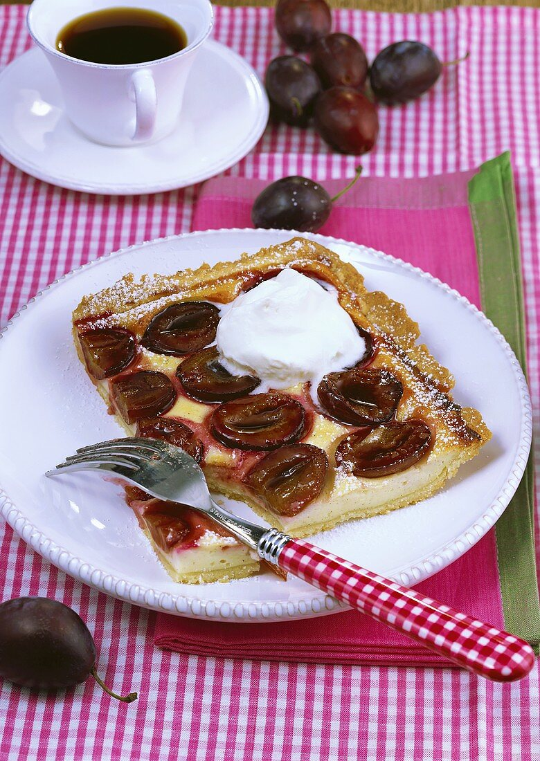 Piece of plum cake with cream, cup of coffee