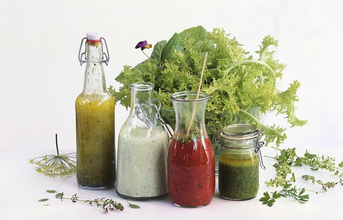 Four different salad dressings in front of salad bowl