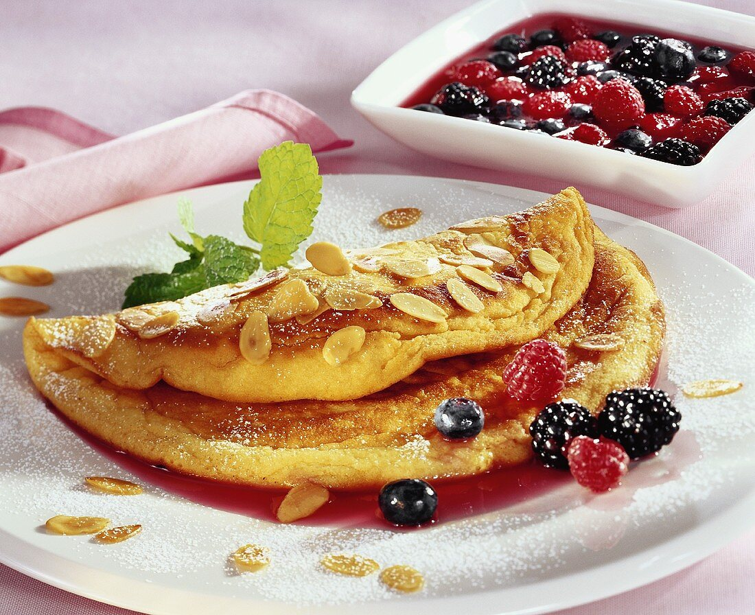 Soufflé omelette with forest fruits and flaked almonds