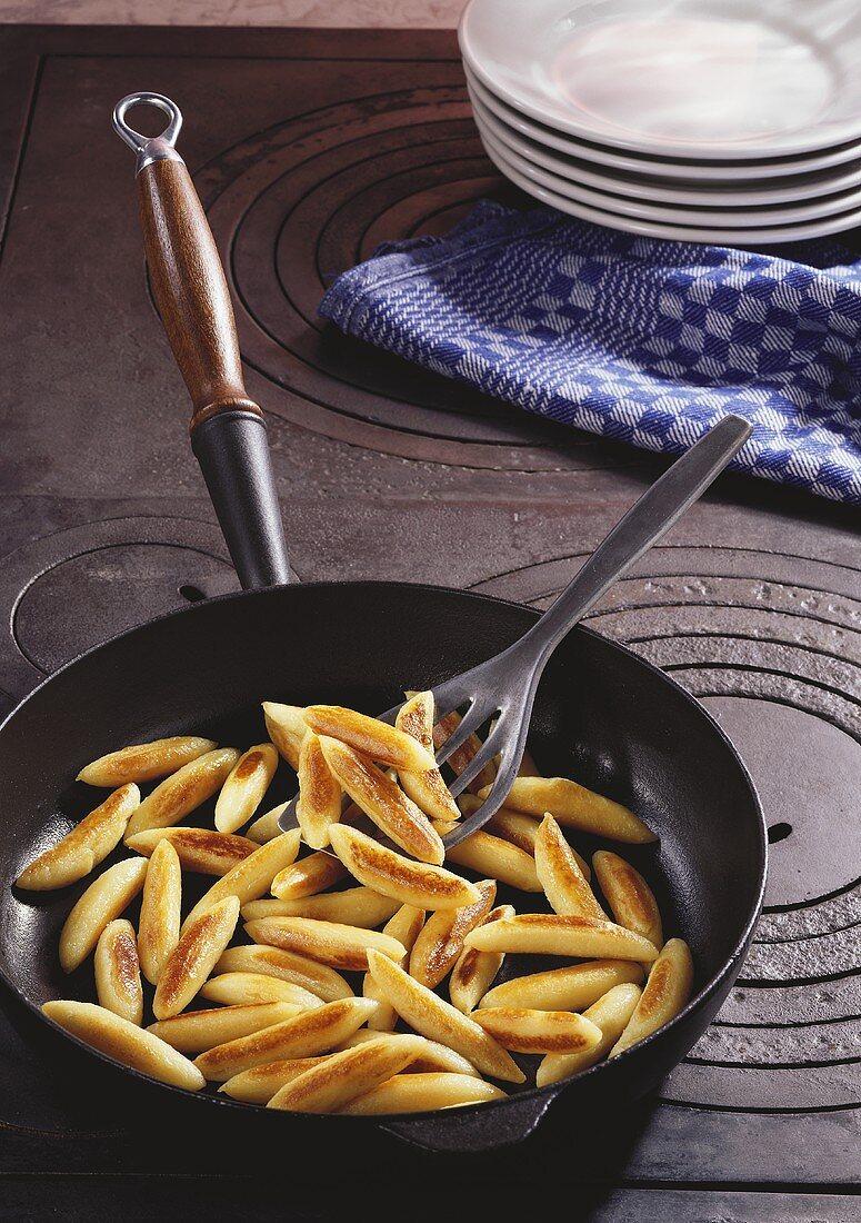 Potato noodles in frying pan on old range