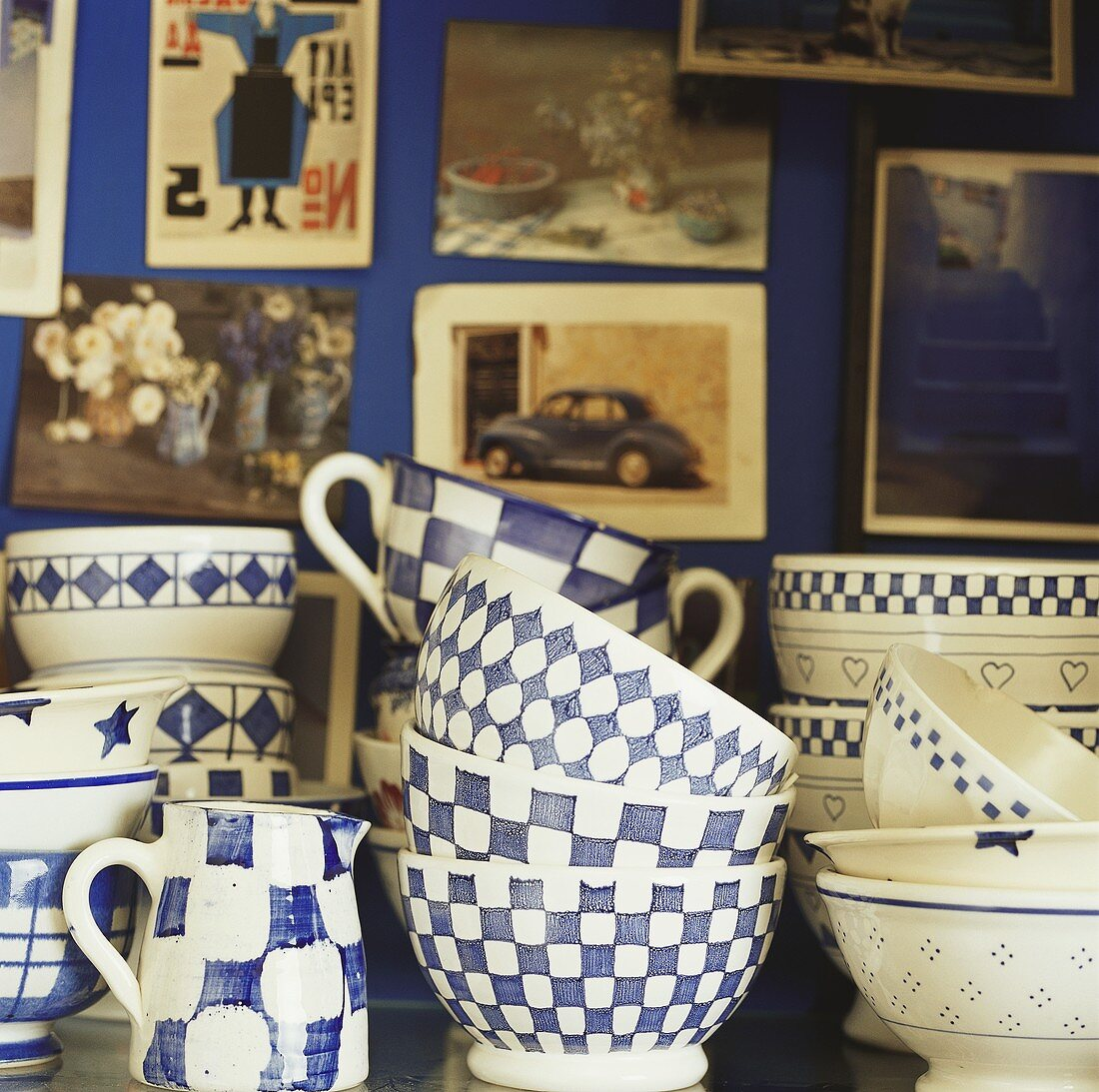 Blue and white crockery in front of wall with photographs