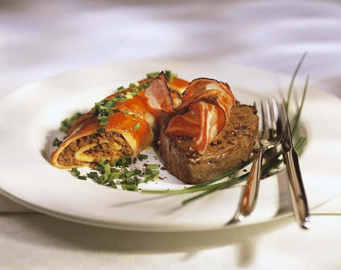 Beef fillet with bacon and pancakes with mince filling