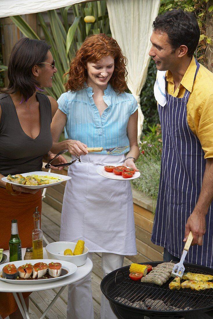 Friends barbecuing food in garden