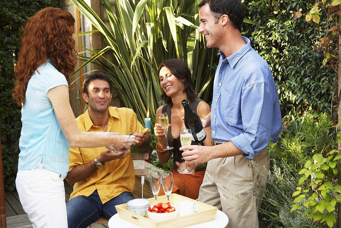 Two couples at party in garden with Sekt & fresh strawberries