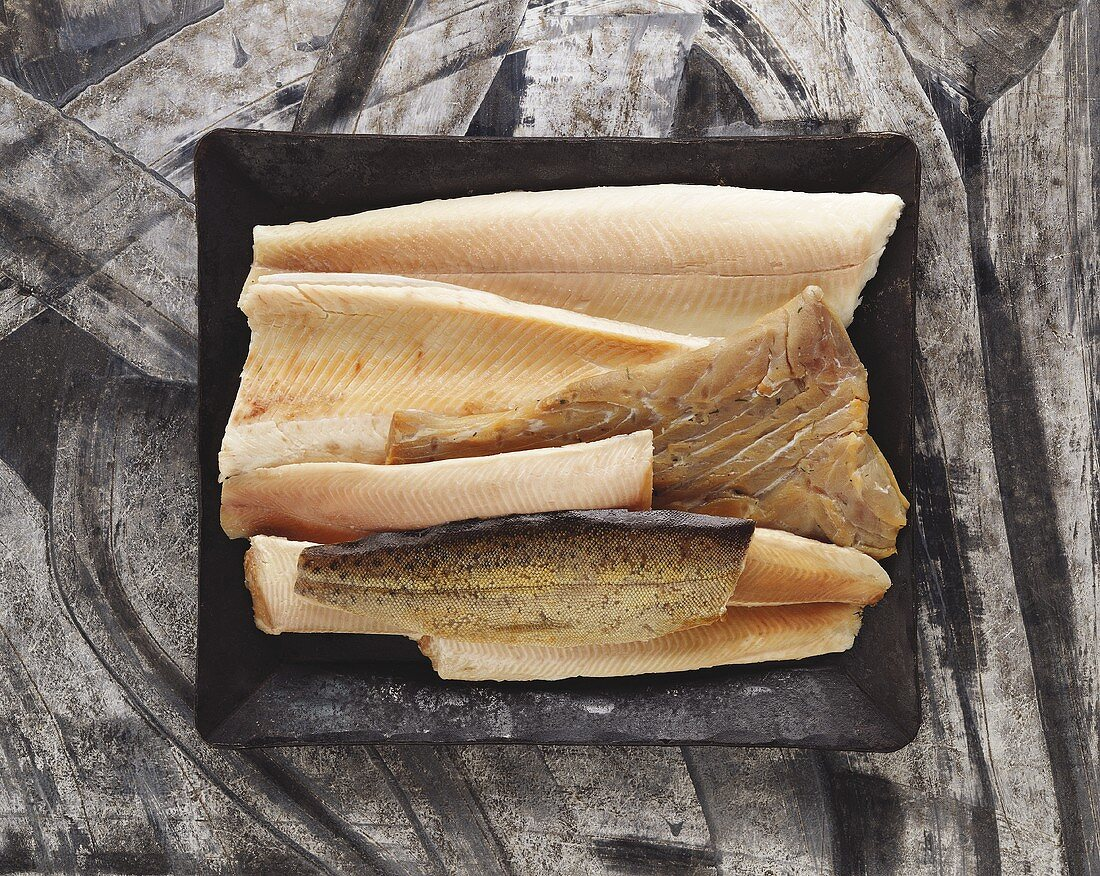 Various types of smoked fish fillets on black platter
