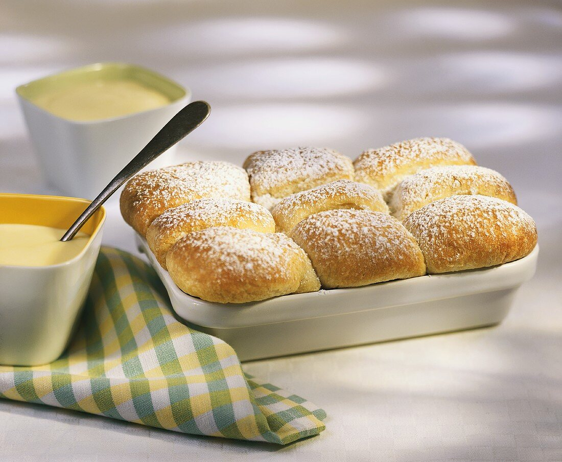 Sweet rolls (Buchteln) with icing sugar and custard