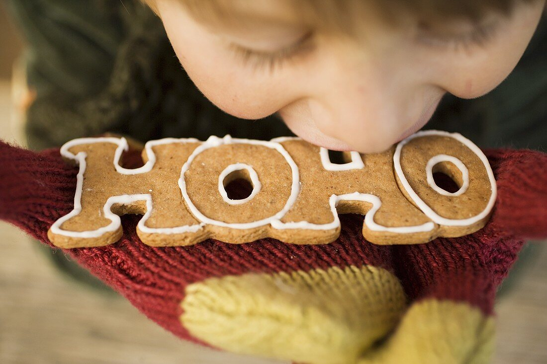Child biting into gingerbread (the word HOHO)