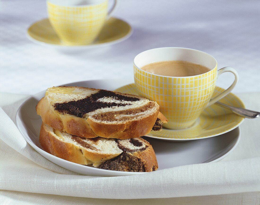 Two slices of bread plait with poppy seed filling, coffee
