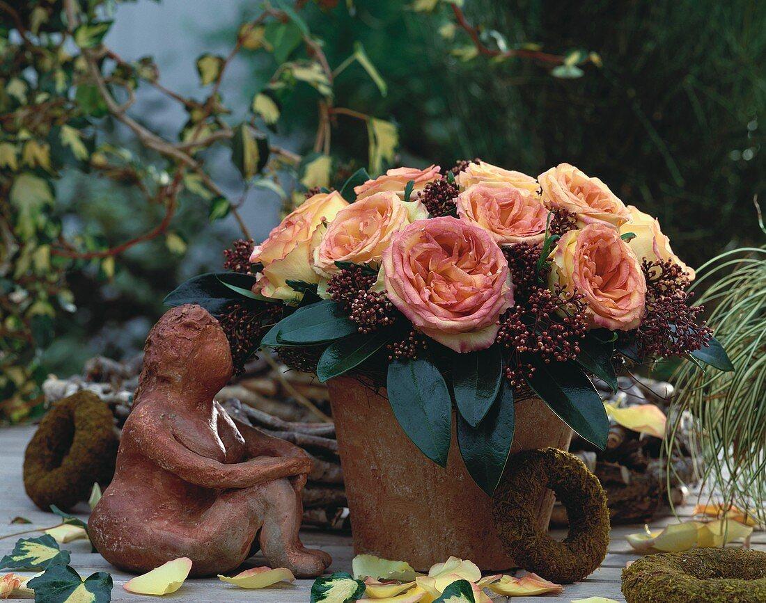 Arrangement of roses in terracotta pot, terracotta figure