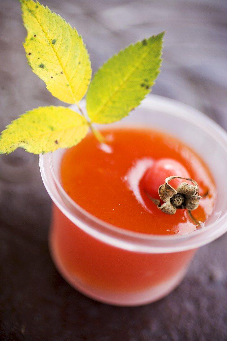 Rose hip jam in jar with fresh rose hip and leaf